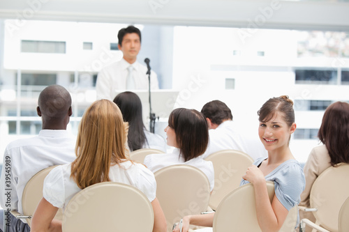 Happy business woman looking behind her during a speech