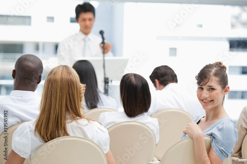 Smiling woman looking behind he during a speech
