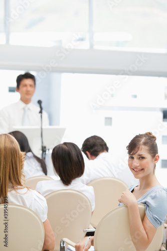 Close-up of a happy businesswoman looking behind her during a speech