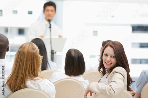 Brown haired businesswoman looking behind her during a speech