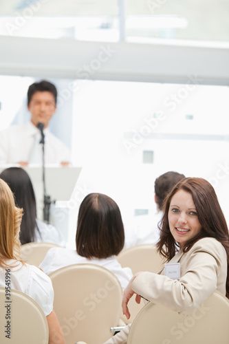 Happy brown haired woman looking behind her during a speech