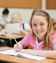 Young female schoolchild sitting at her desk
