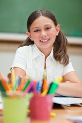 Smiling student next to pencil holders