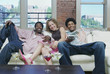 Portrait of group sitting on couch laughing