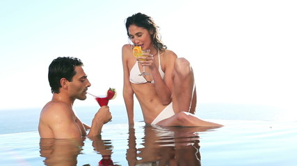 Couple holding cocktail glasses in a swimming pool
