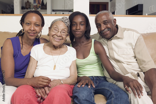 Couple sitting with their teenage daughter and mother in-law on a couch