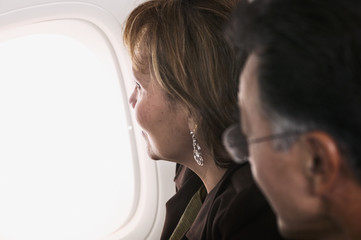 Profile of couple looking out airplane window