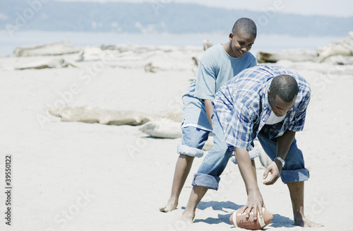 Father and son playing football on the beach