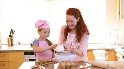 Smiling mother and daughter cooking together