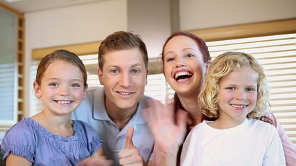 Smiling family waving their hands