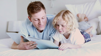 Father and son smiling while reading a book