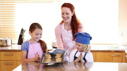 Smiling mother giving cookies to her children