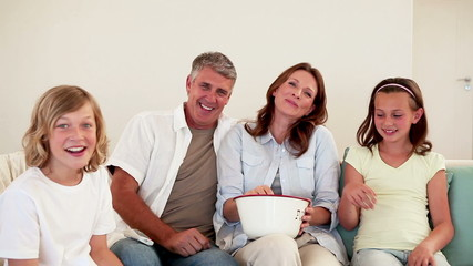 Family laughing while watching television