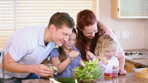 Family making a salad with vegetables