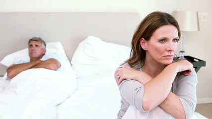 Upset couple sitting on a bed