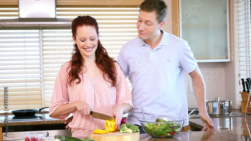 Woman chopping peppers in front of her boyfriend