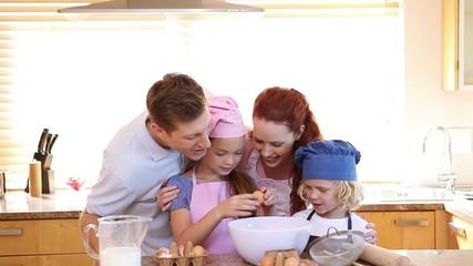 Little girl breaking eggs with her family