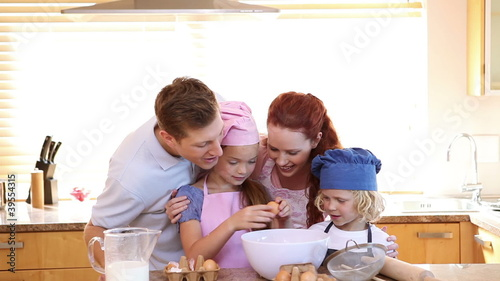 Little girl breaking eggs with her family