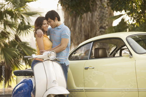 Couple hugging by car and scooter