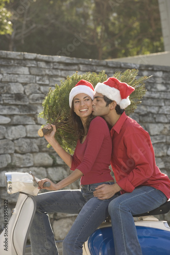 Couple wearing Santa hats on scooter