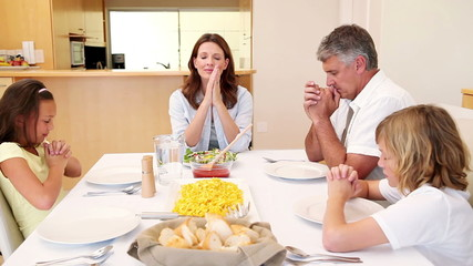 Family praying before having dinner