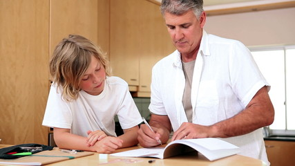 Father and son doing homework in the kitchen