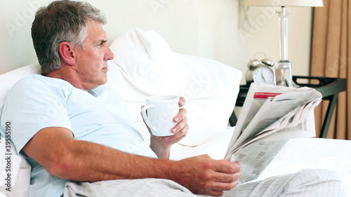 Man reading a newspaper in his bed