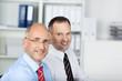 portrait von zwei lächelnden geschäftsmännern im büro