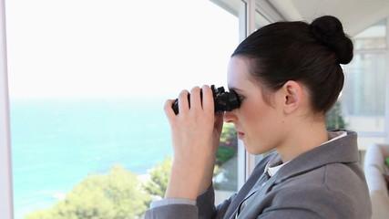 Businesswoman looking through a binoculars