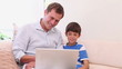 Father and son with laptop in the living room