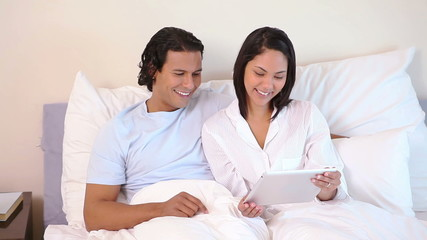 Couple sitting on their bed with tablet computer