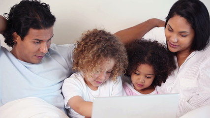 Family with laptop on their bed