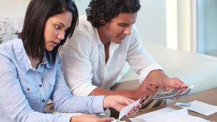Young couple with paperwork using laptop