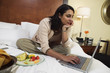Businesswoman with laptop and food on hotel bed