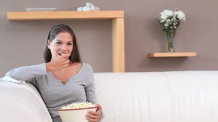Brunette woman eating popcorn