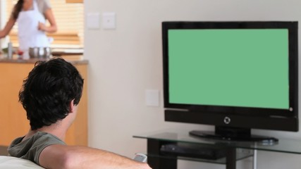 Man watching the television while his wife is cooking
