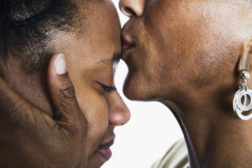 Close up of mother kissing daughter's forehead