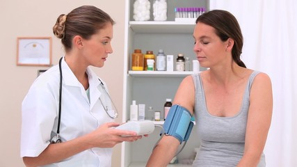 Nurse taking the blood pressure of a patient
