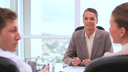 Smiling businesswoman talking with customers