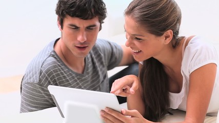 Smiling couple using a tablet pc