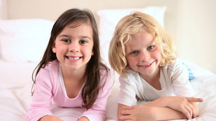 Smiling siblings lying on a bed