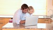Smiling father and son using a laptop