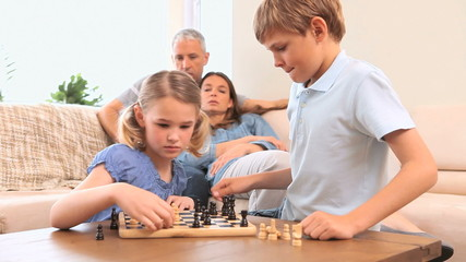 Smiling siblings playing chess