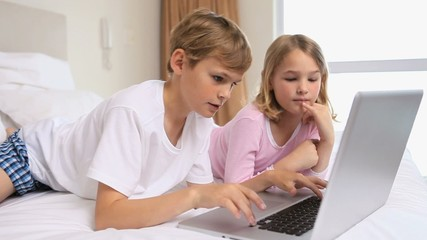Happy siblings using a laptop
