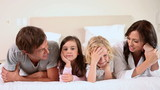 Family lying together on a bed
