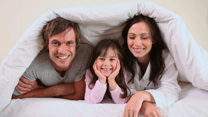 Family lying in a bed