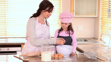 Mother helping her daughter to cook
