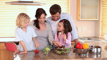 Smiling family making a salad