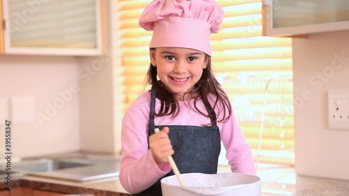 Smiling little girl cooking