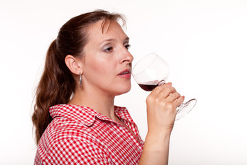 Woman in a red checked shirt drinking red wine